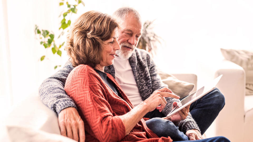 Senior couple with tablet sat in a chair
