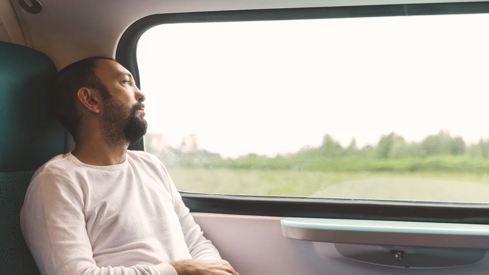 Man thinking on train
