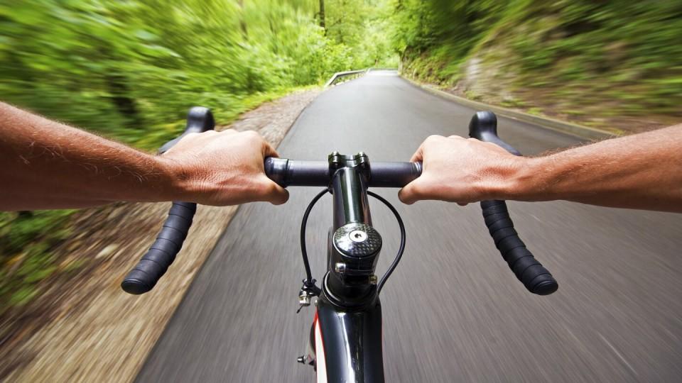 Newsroom - Man holding bike handles on a road