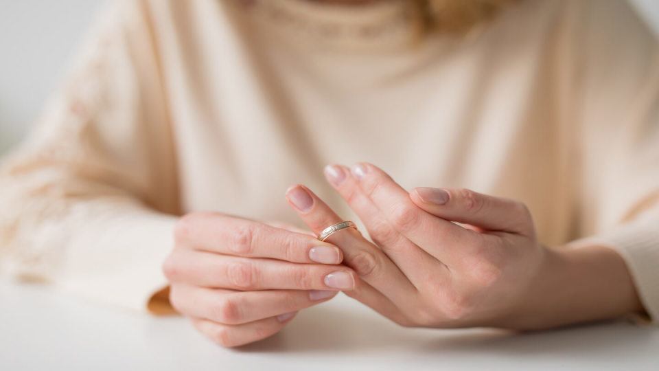Woman pulling at wedding ring on hand