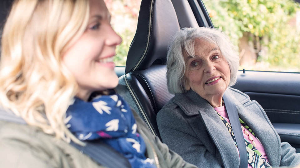 Woman and elderly passenger in car drive driving