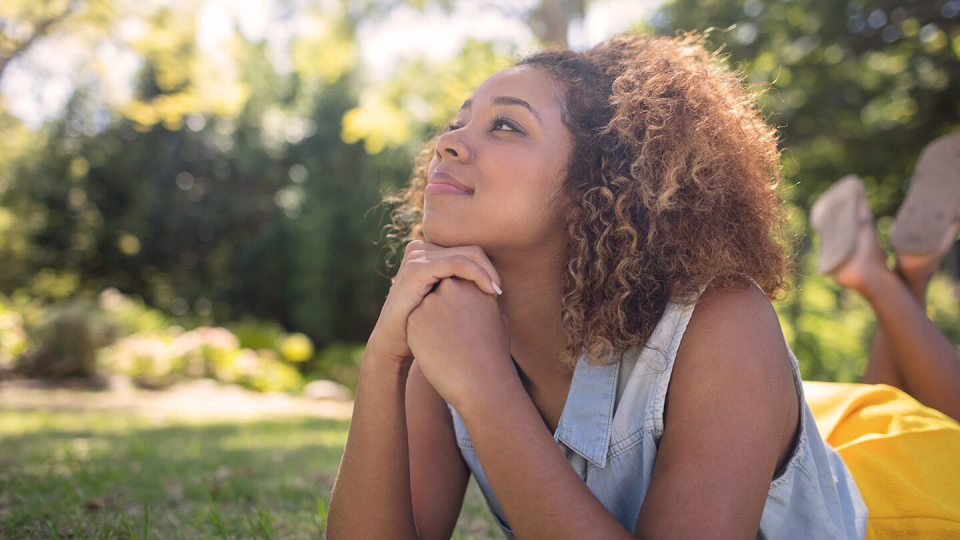 Young woman daydreaming in garden