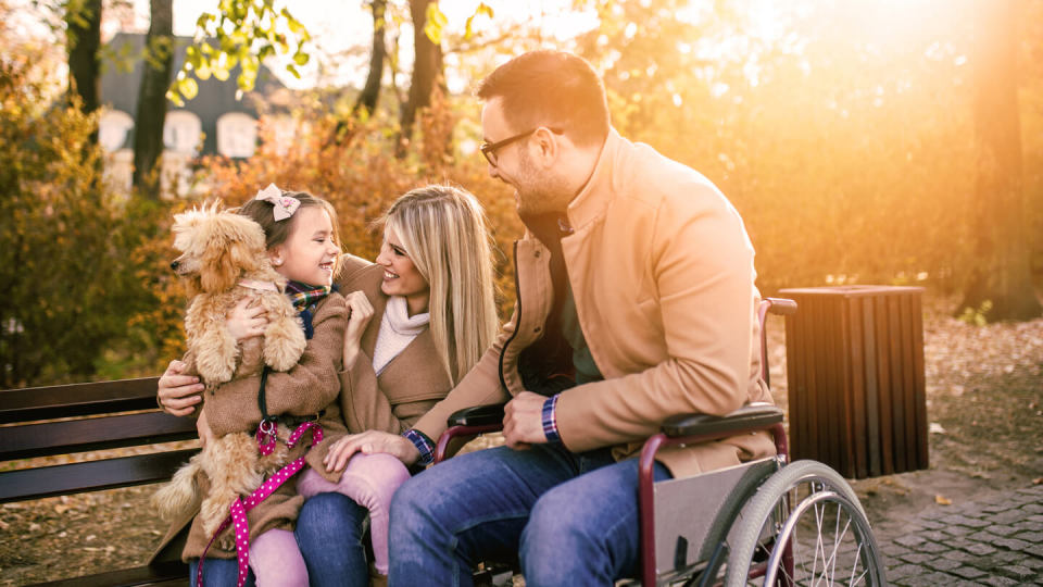 Disabled father in wheelchair with his daughter, wife and dog in the park