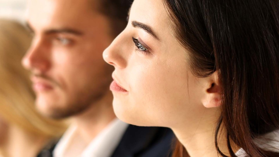 Woman listening to someone with man in background