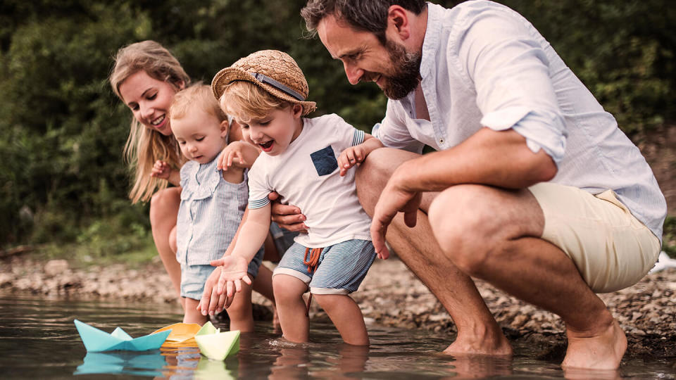 Young family with two children playing in the water