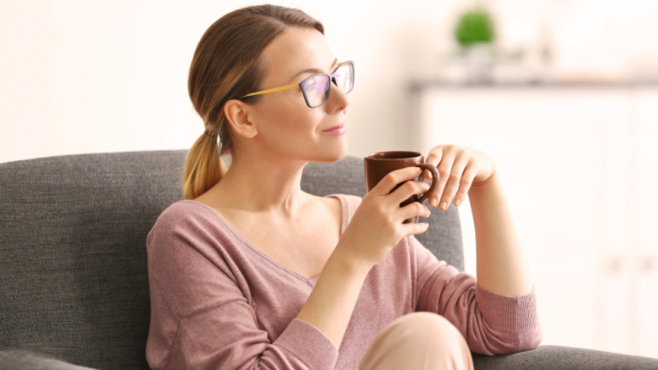 Woman in glasses drinking coffee