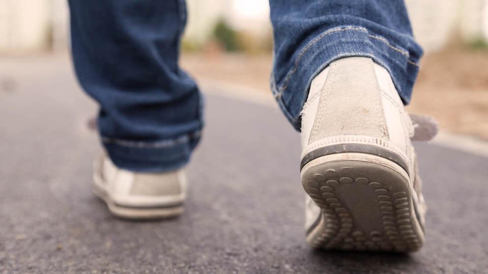 Newsroom - man's feet walking on pavement