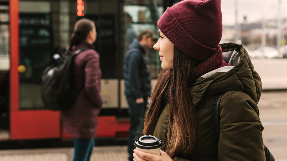 Woman holding coffee in front of bus