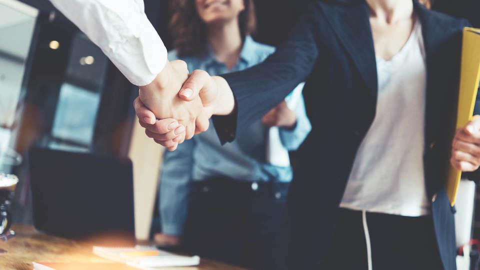 Newsroom office workers shaking hands