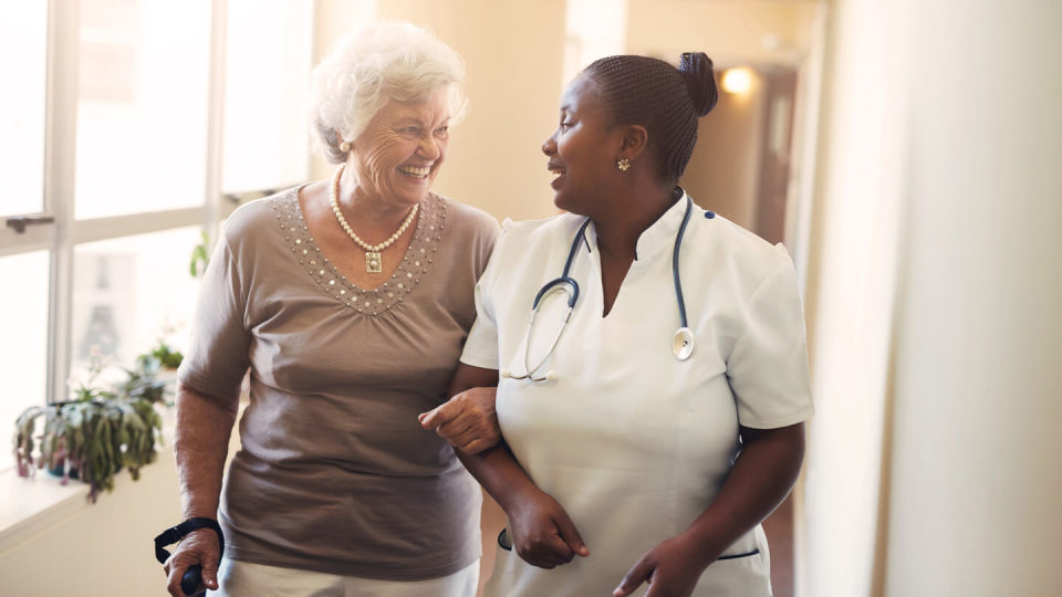 Happy nurse talking to elderly lady