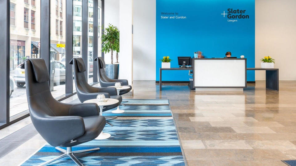 Large open office lobby with reception desk and comfy chairs
