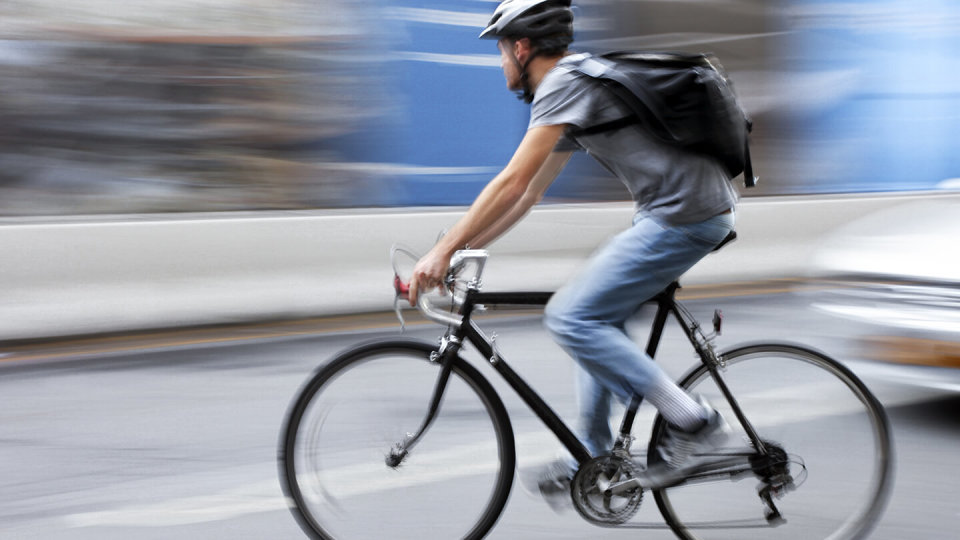 Man riding bike fast in middle of road