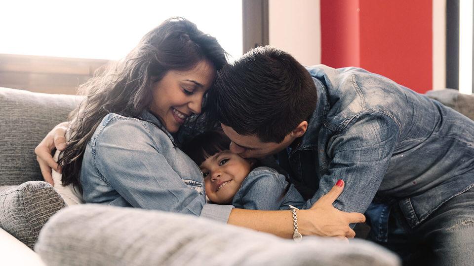 family hugging on sofa