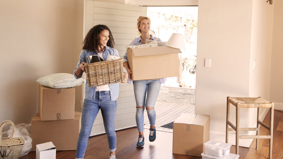 Two women carrying boxes into a home