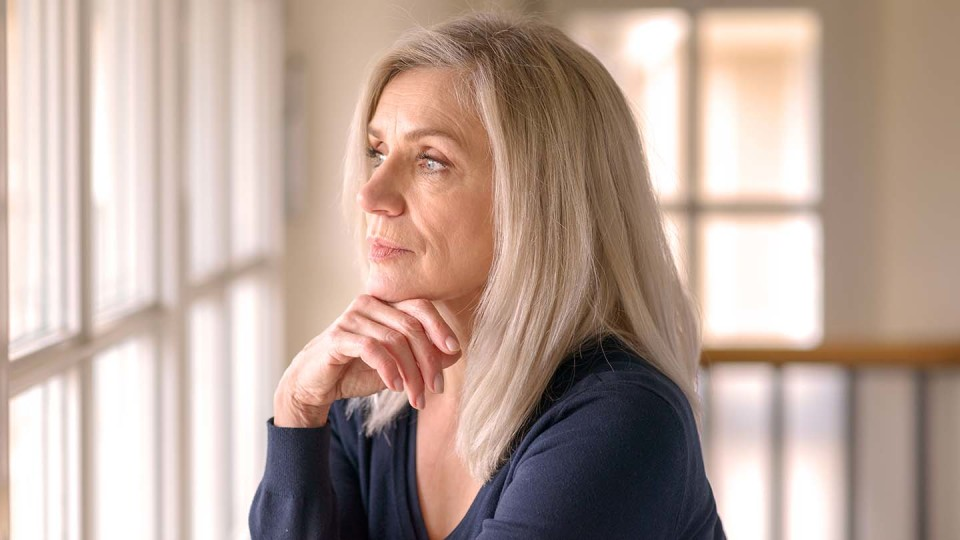 Older looking blond lady looking out of window