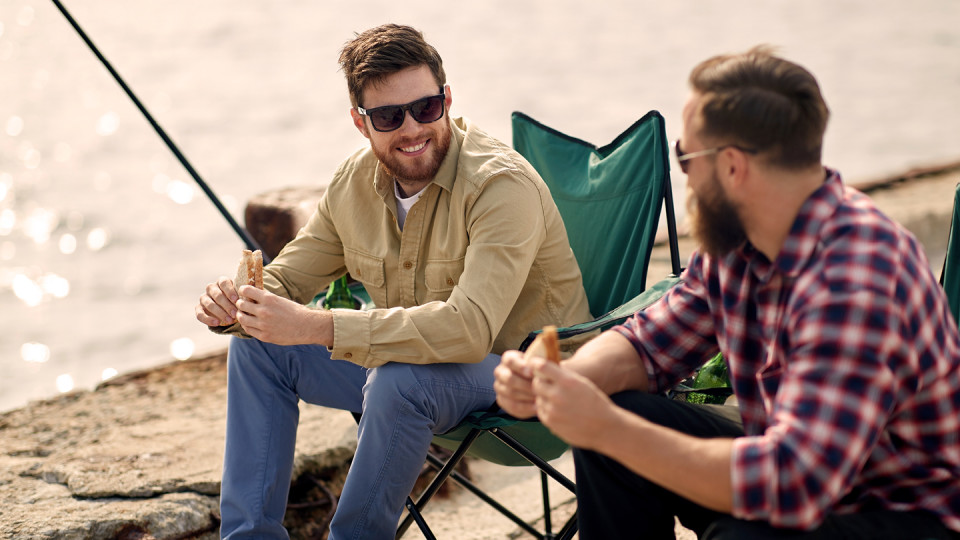 Men eating sandwiches and fishing