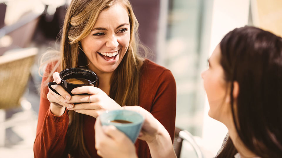 Young women smiling over coffee