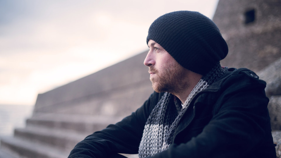 Young man sitting outside on chilly day