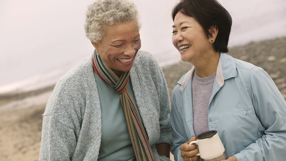 Happy mature women laughing on a beach