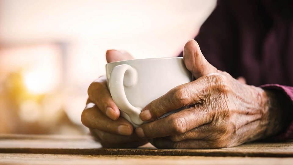 Newsroom - elderly hands holding cup of tea
