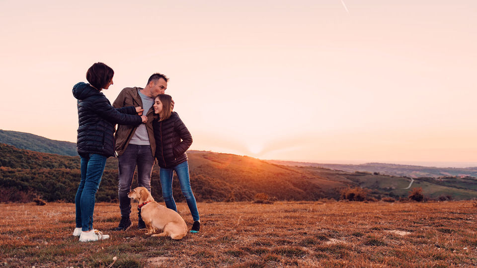 Family with dog on a hill