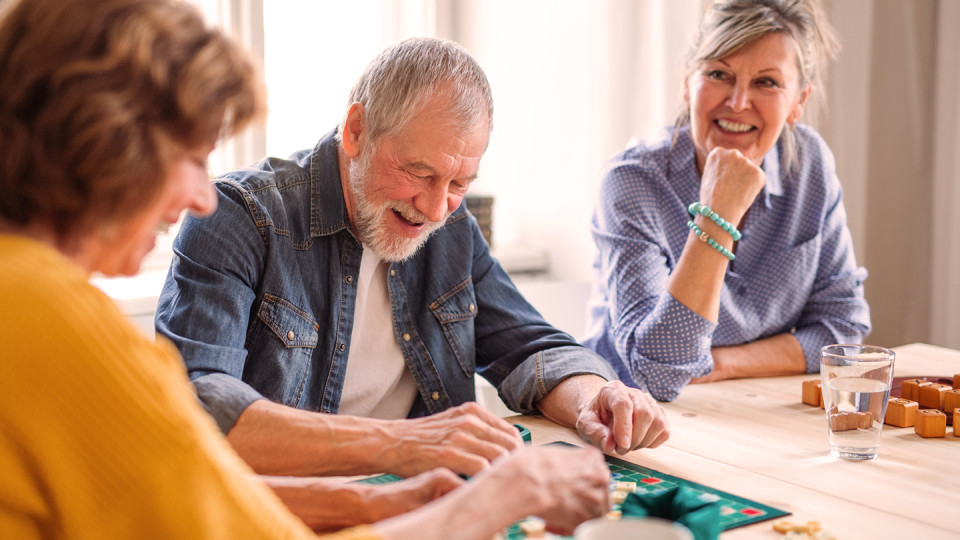 Man playing board game with two women