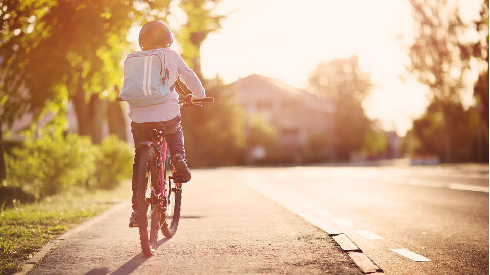 Newsroom - child on bicycle on pavement