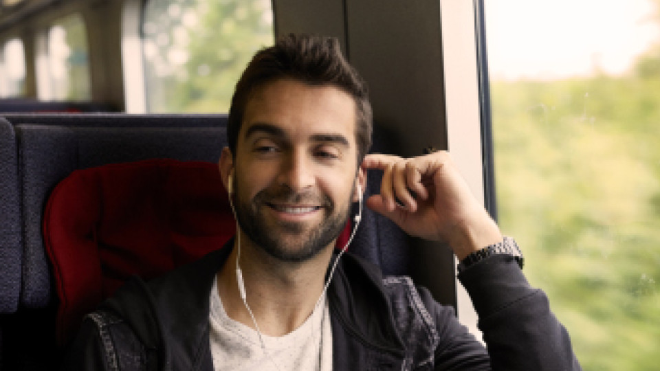 Man on train with headphones in